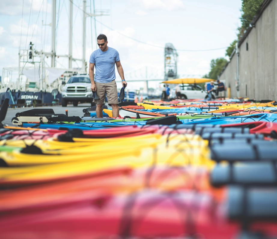A man walking down a long line of sea kayaks lying on the wharf