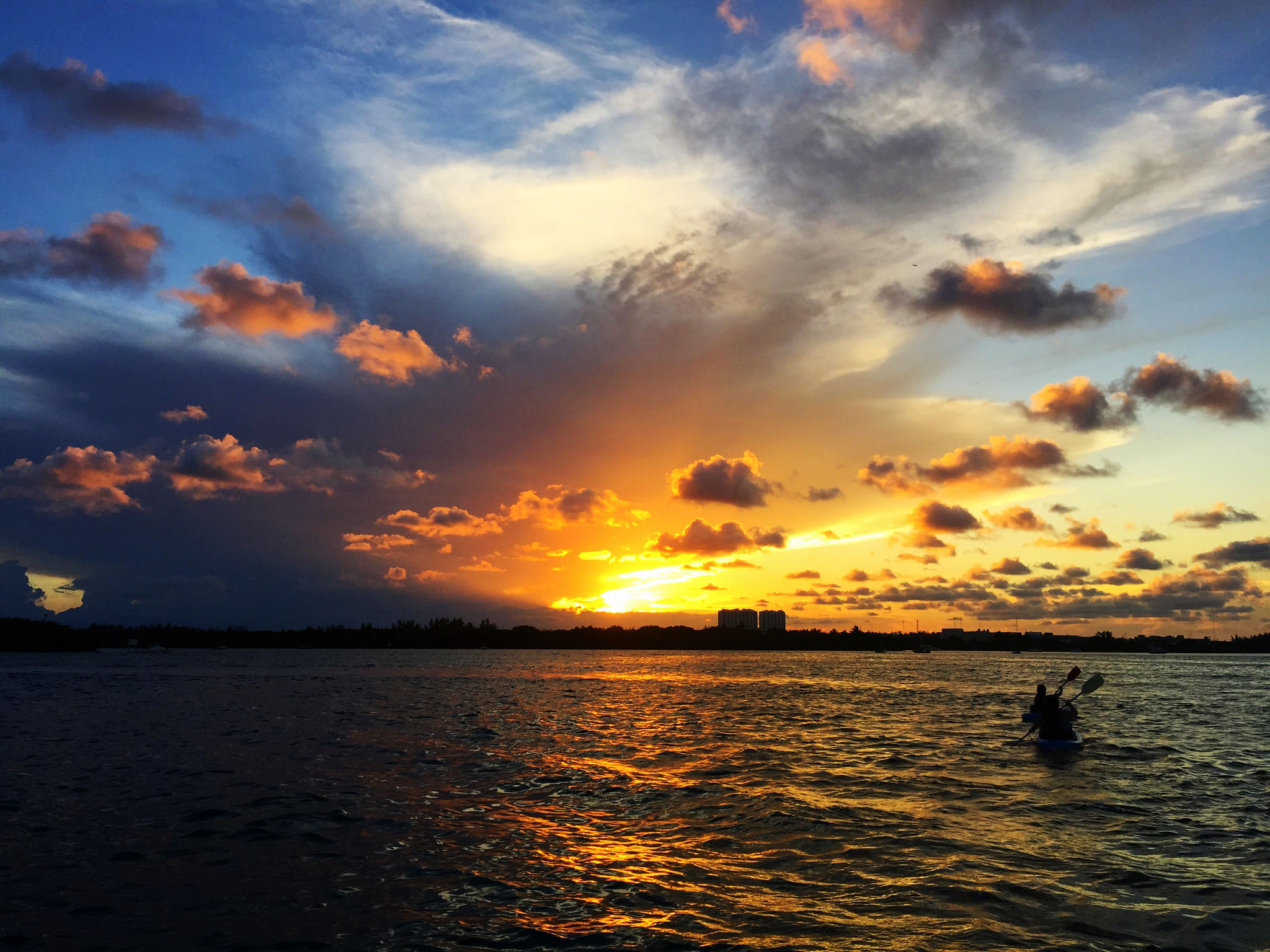 A kayaker paddles into the sunset.