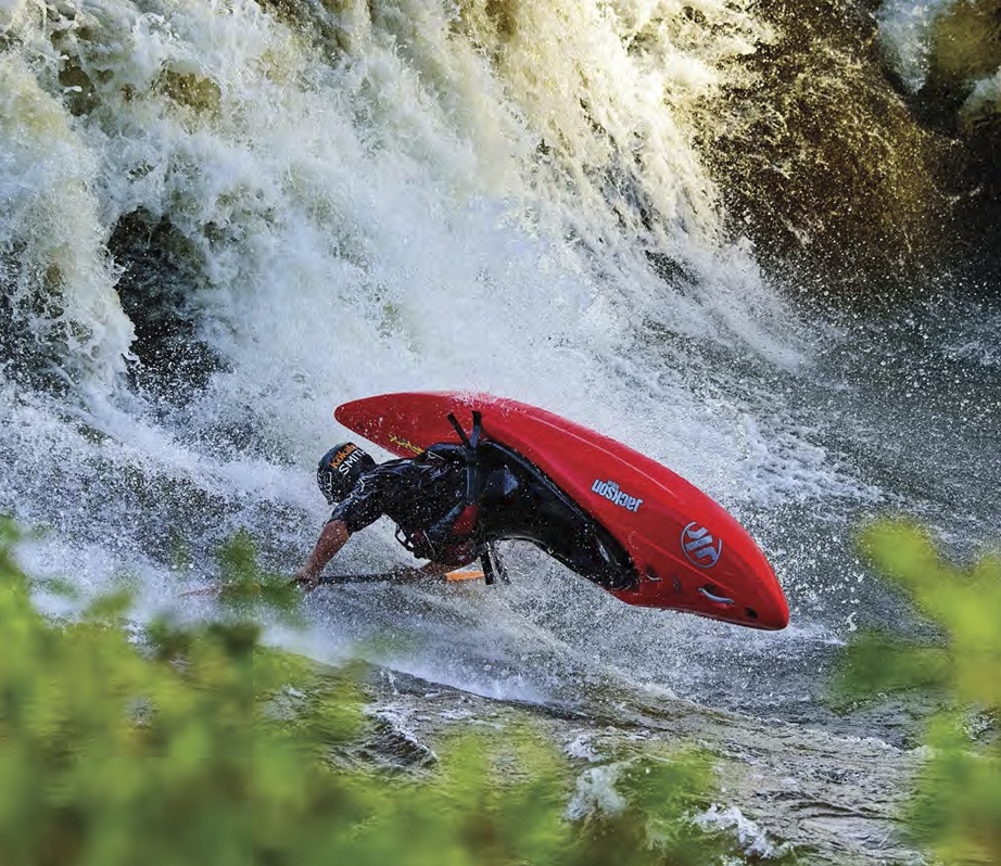 A person flipping in a whitewater kayak.