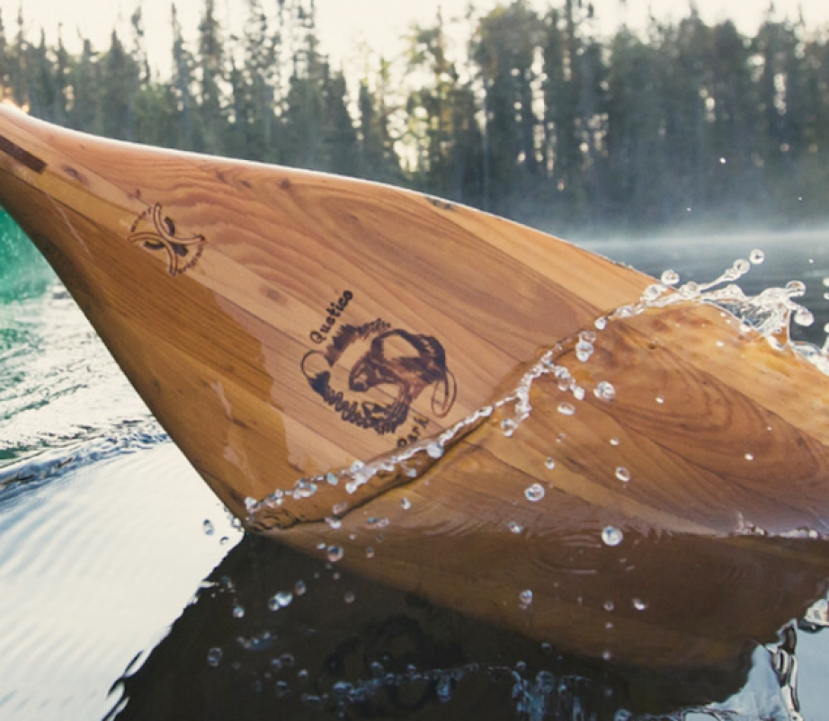 a wooden canoe paddle being used to paddle on a lake