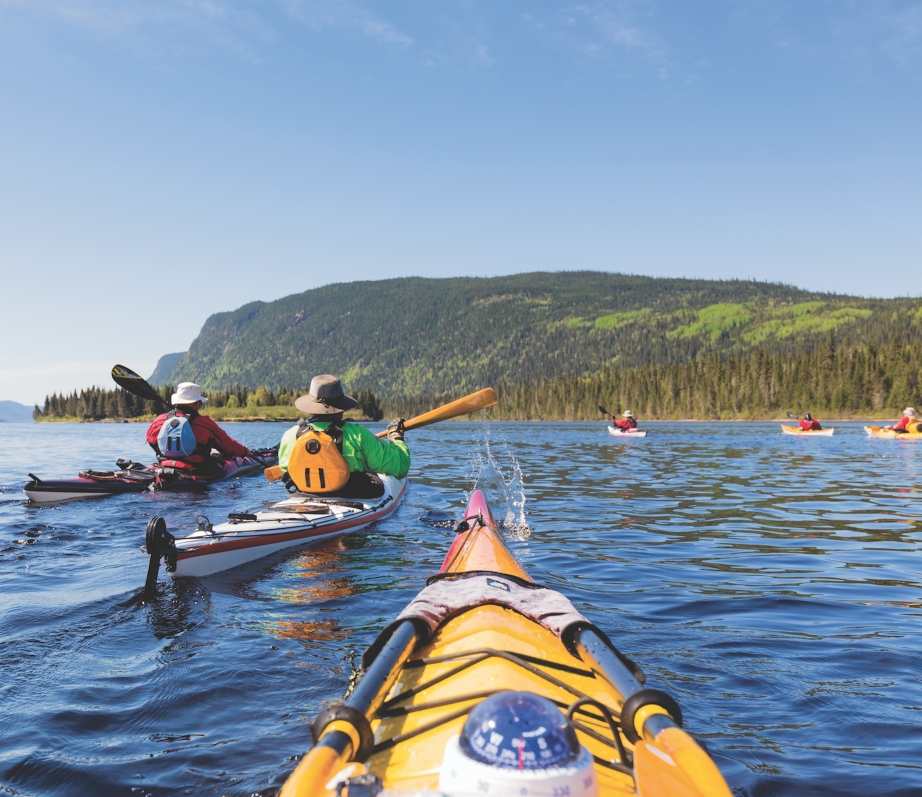 A group of sea kayakers paddle on a large body of water