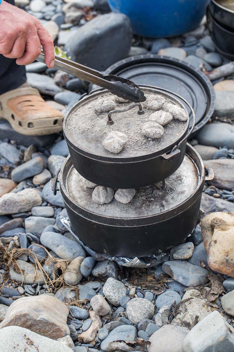 Lasagna cooks in a dutch oven at a canoe campsite.