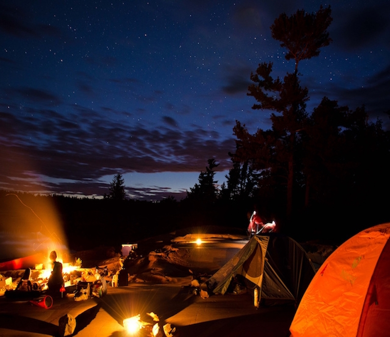 An orange tent by a campfire during the evening.