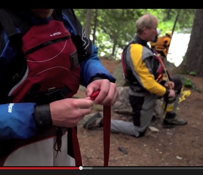 A whitewater kayaker holds a flip line in his hands.