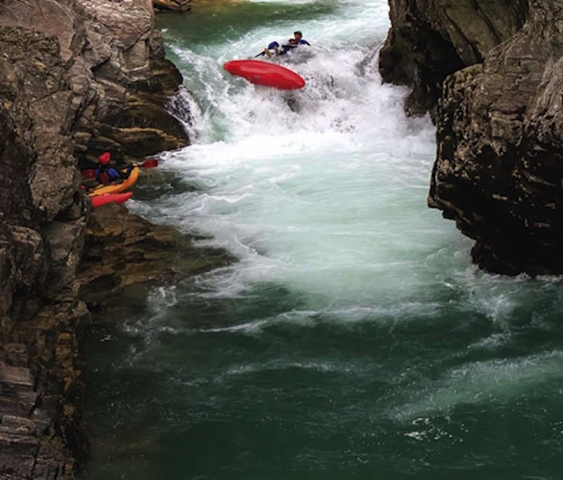 A kayaker in a red boat goes down a big raoid.