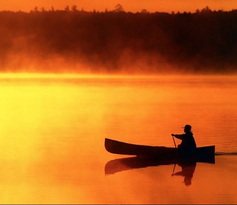 A solo canoeist paddles against an orange sunset.