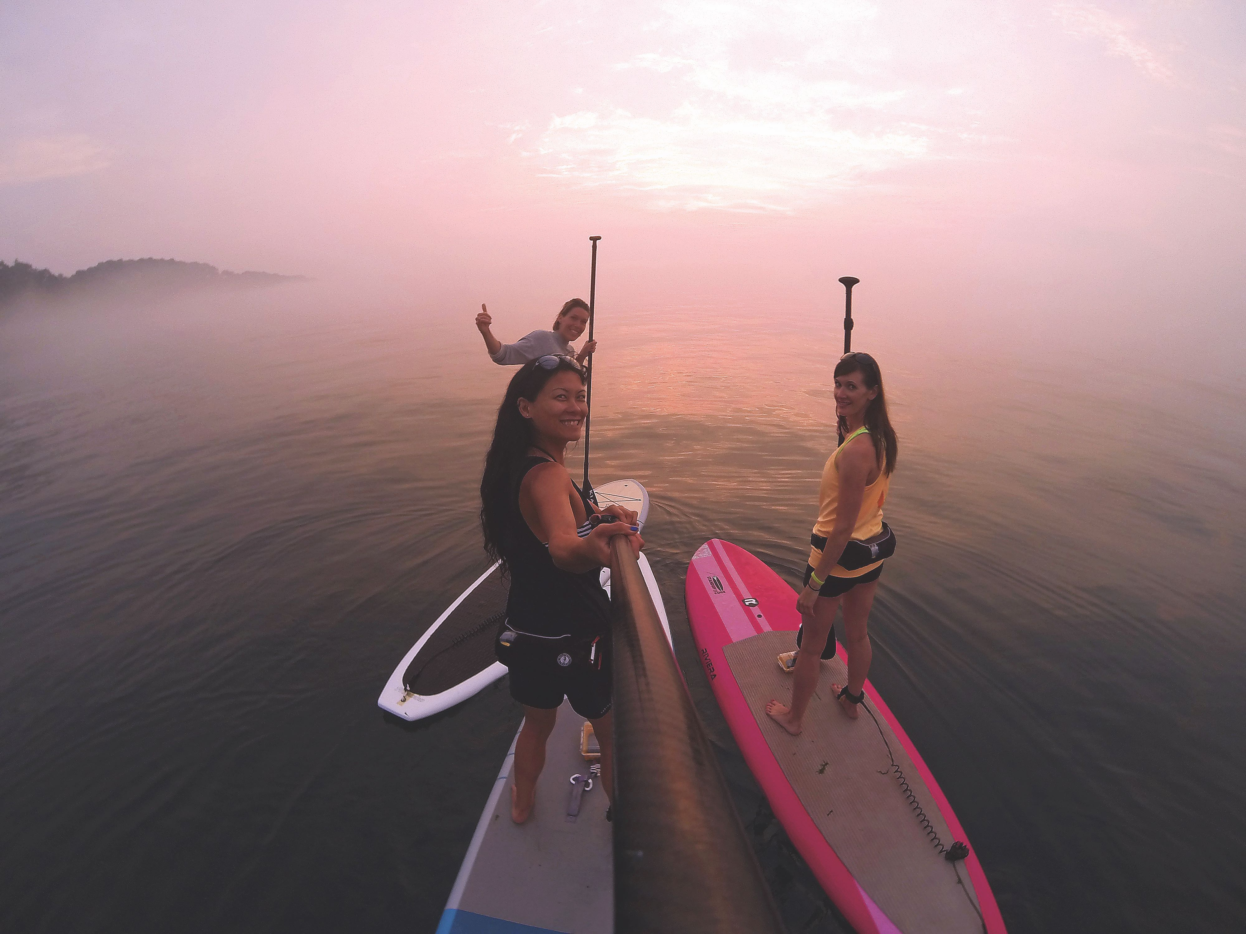 Diana Lee and two women standing on their paddleboards and smiling at the camera with a sunset in the backgroun