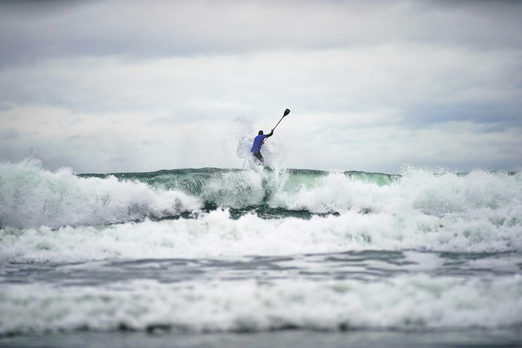 man bursting through waves on his surfing SUP with his SUP paddle in the air