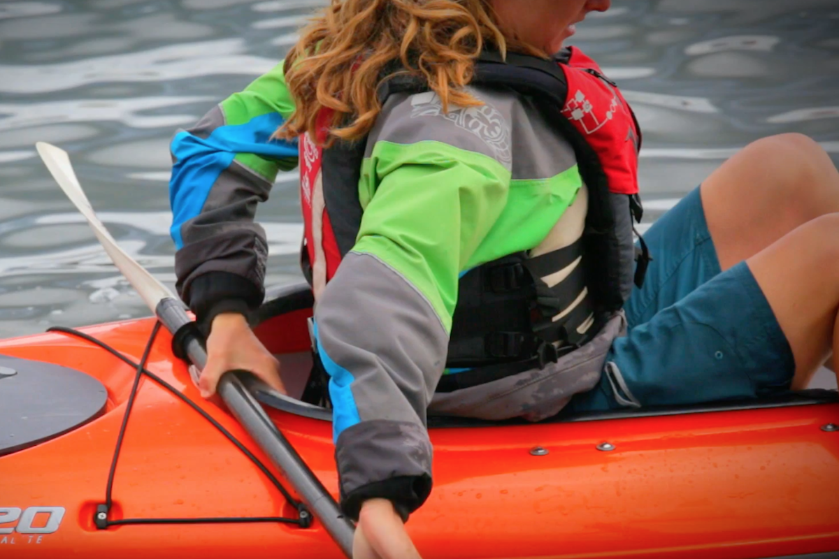 A female paddler uses her paddle to sit down inside her rec kayak.