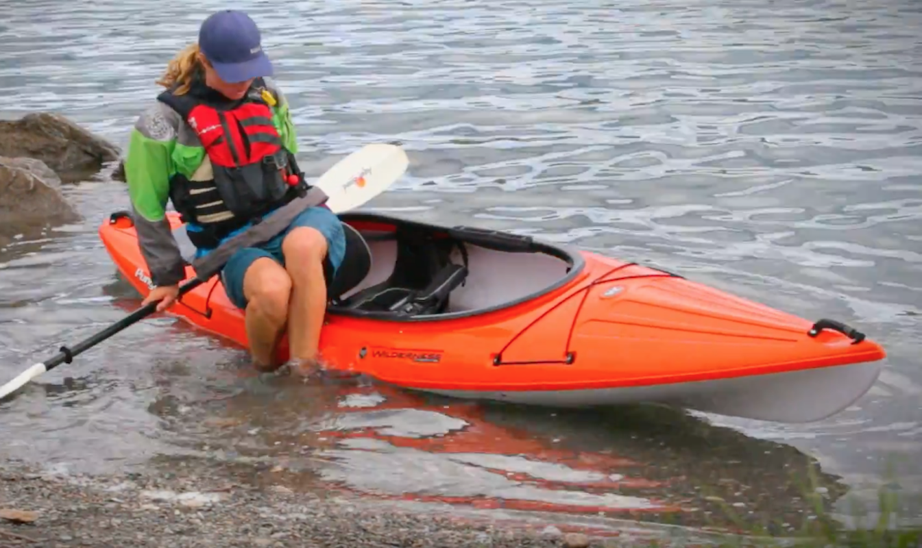 A female paddler braces herself on her kayak paddle to get inside a rec kayak.