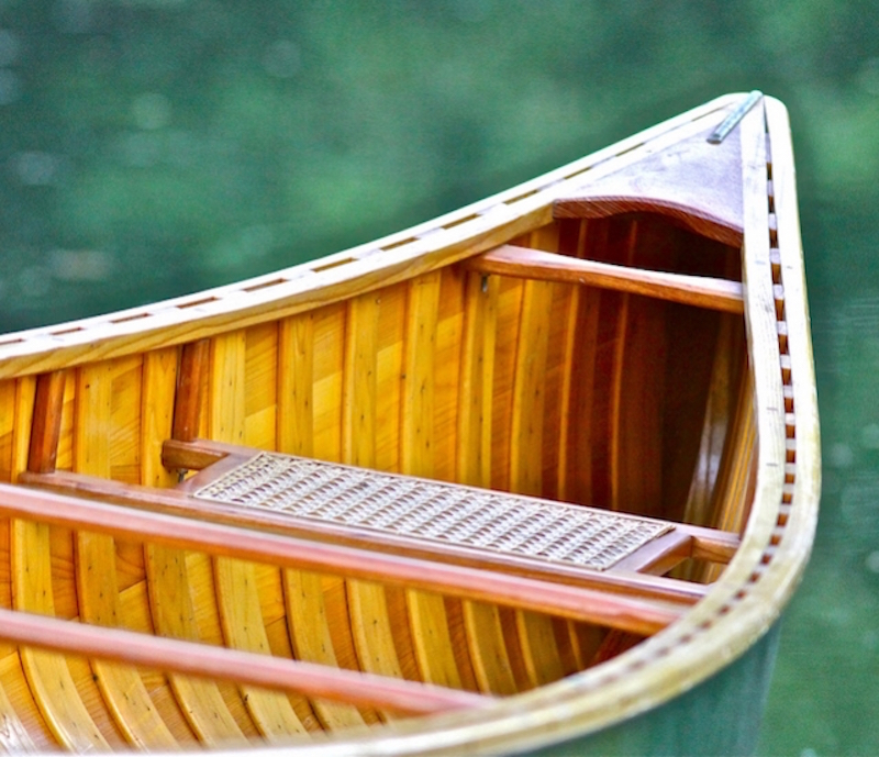 A wooden canoe against a blurred green background.
