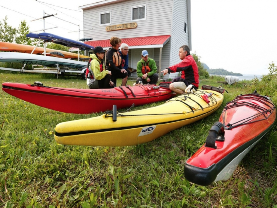 paddlers talking amongst several different sea kayaks