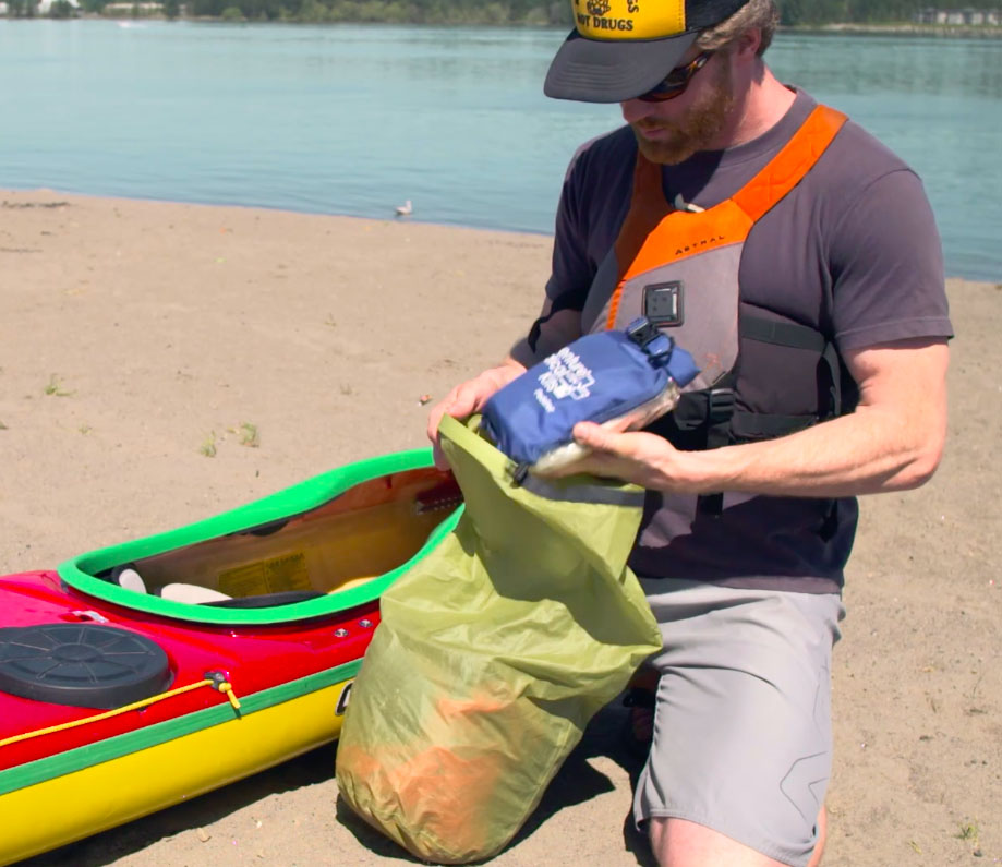 A paddler fills a dry bag with extra clothes.
