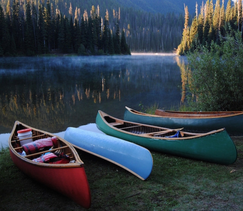 A collection of colorful canoes against a foggy morning lake.