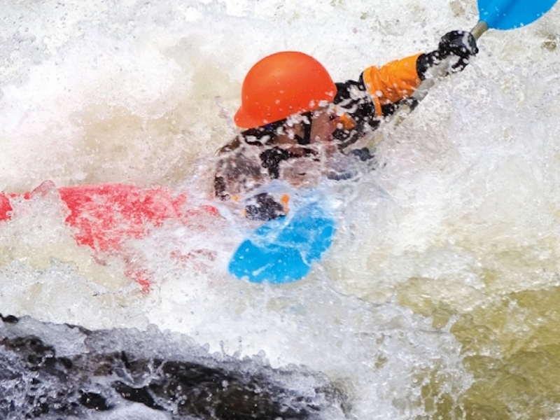 A kayaker in an orange helmet is stuck in a hole on a whitewater river.