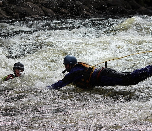 A whitewater kayaker rescuing another paddler in a rapid.