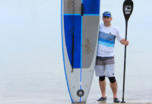 Dan Dakin holding up a paddleboard and paddle