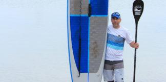 Dan Dakin holding up a paddleboard and paddle