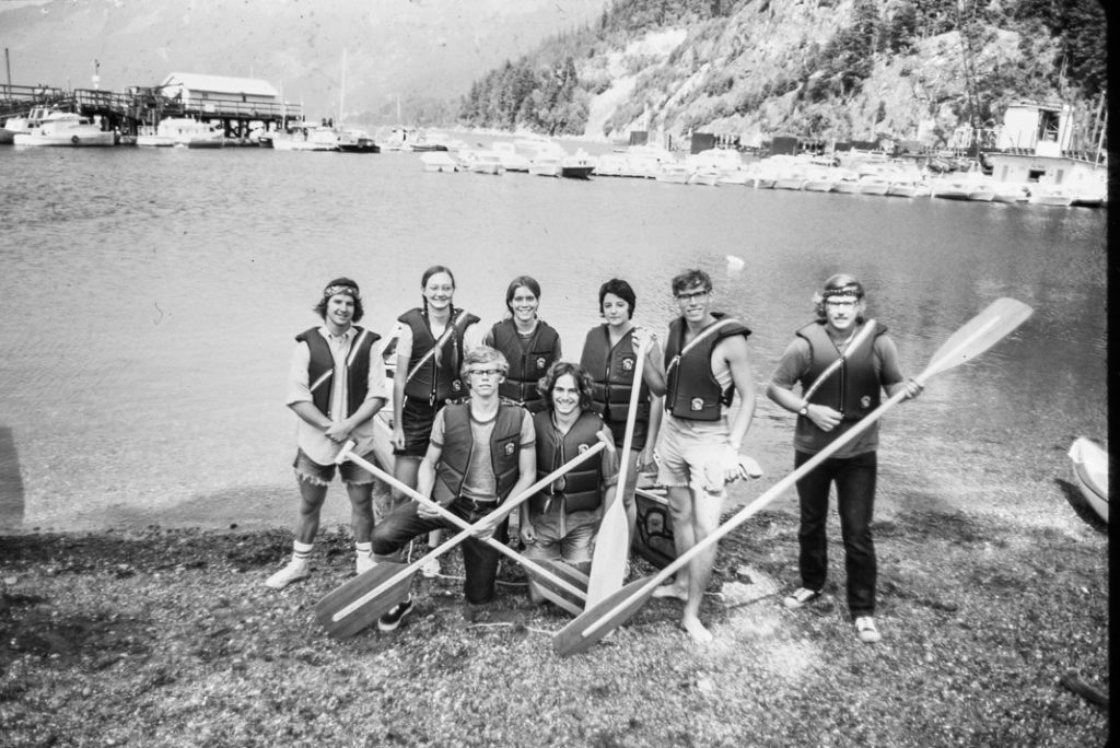 group of people wearing life jackets and holding paddles