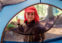 boy standing outside of a tent
