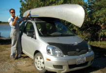 man standing next to his car with a canoe strapped on top