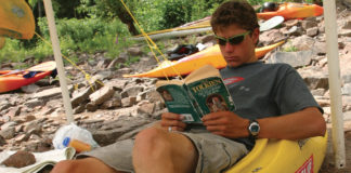 man sitting in kayak reading Fellowship of the ring