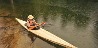 Man paddling a long wooden canoe