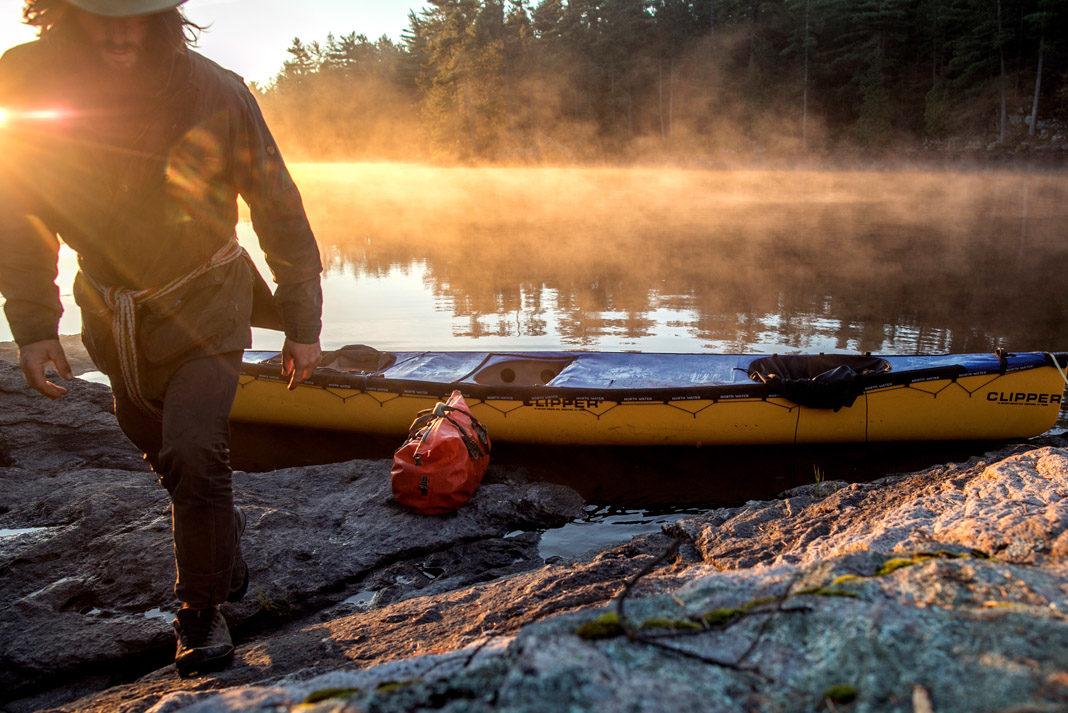 David Jackong walking away from his yellow canoe beside a lake in Canada