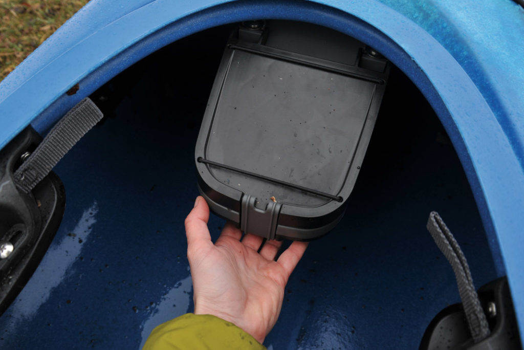 hand holding a waterproof box in a kayak