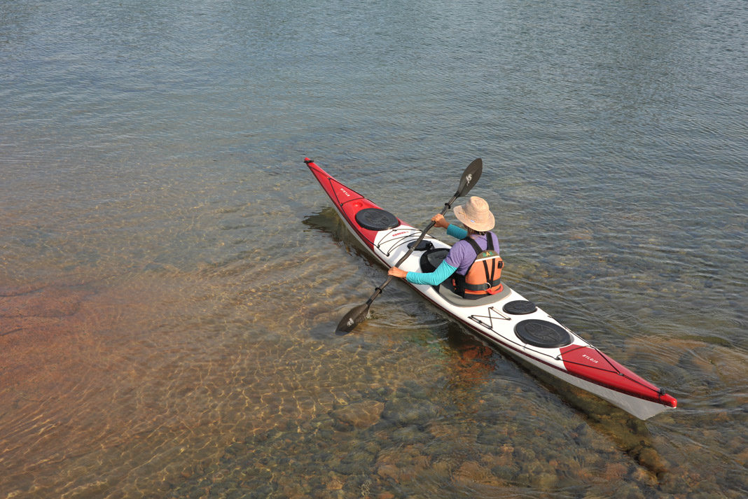person paddling a red and white norse kayak
