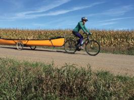 woman on a bike shuttling a canoe