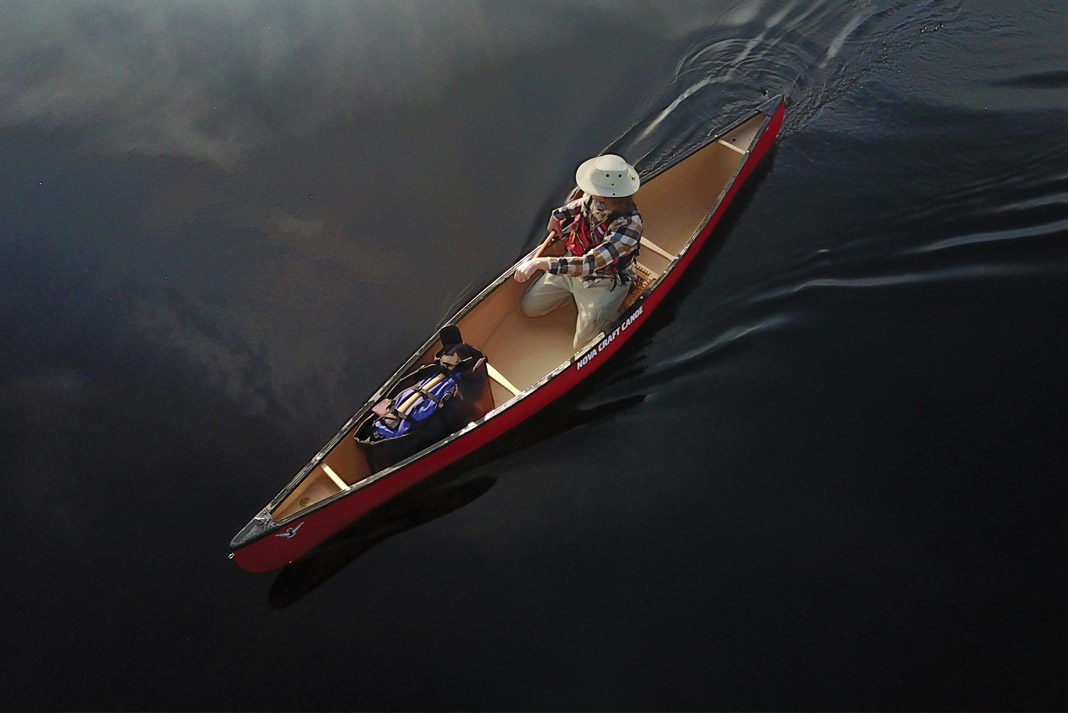 Ariel view of a man paddling canoe on a lake