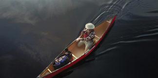 Ariel view of a man paddling canoe on a lake