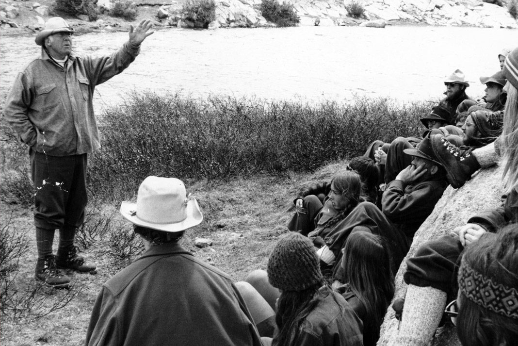 Paul Petzoldt talking to several paddlers in front of a lake