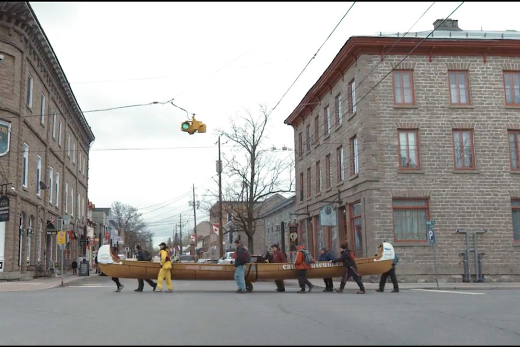 several people carrying a large canoe in the streets