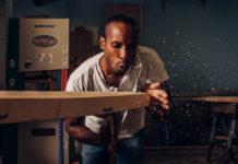 man carving a paddleboard