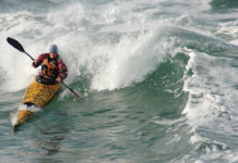 woman in sea kayak surfing a wave