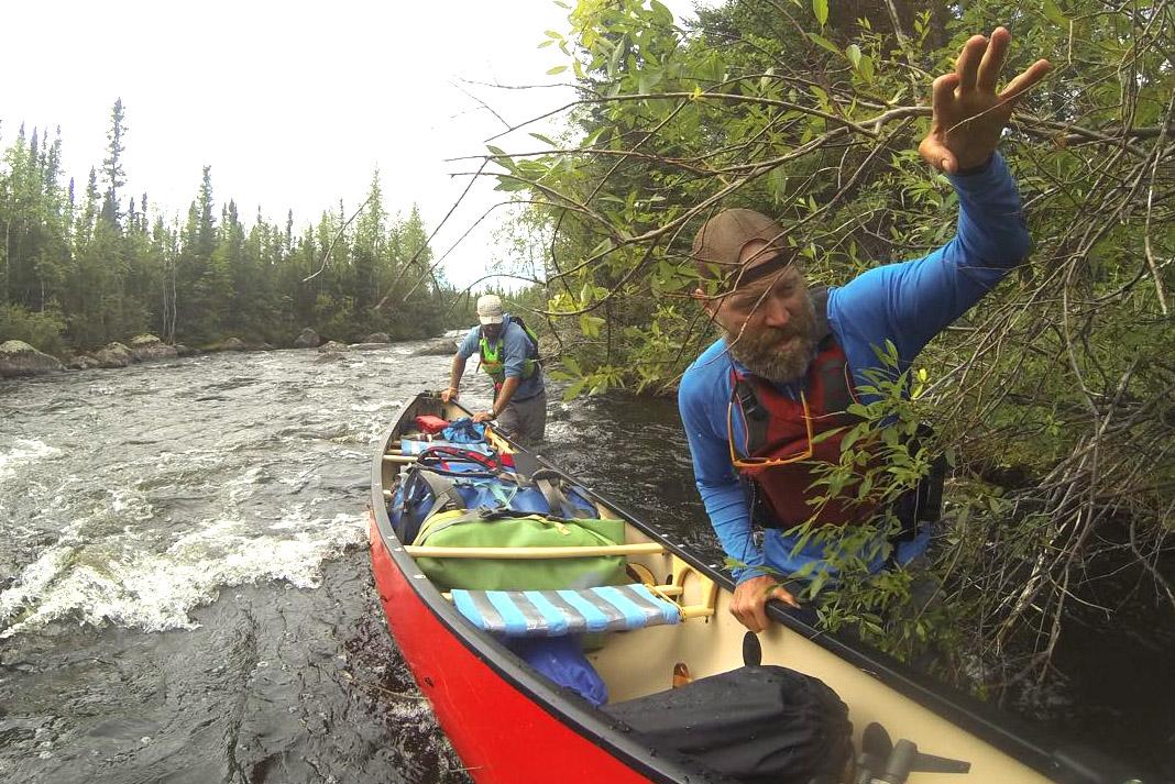 men portaging a canoe down a rapid