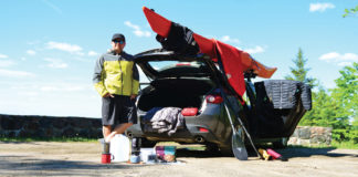 man standing next to his hatchback surrounded by paddling gear