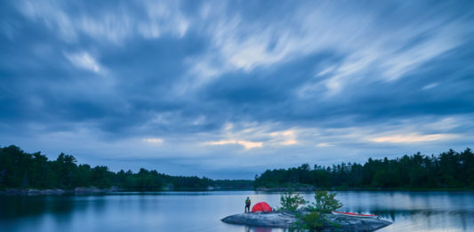 man on a small island with a tent and sea kayak on a lake