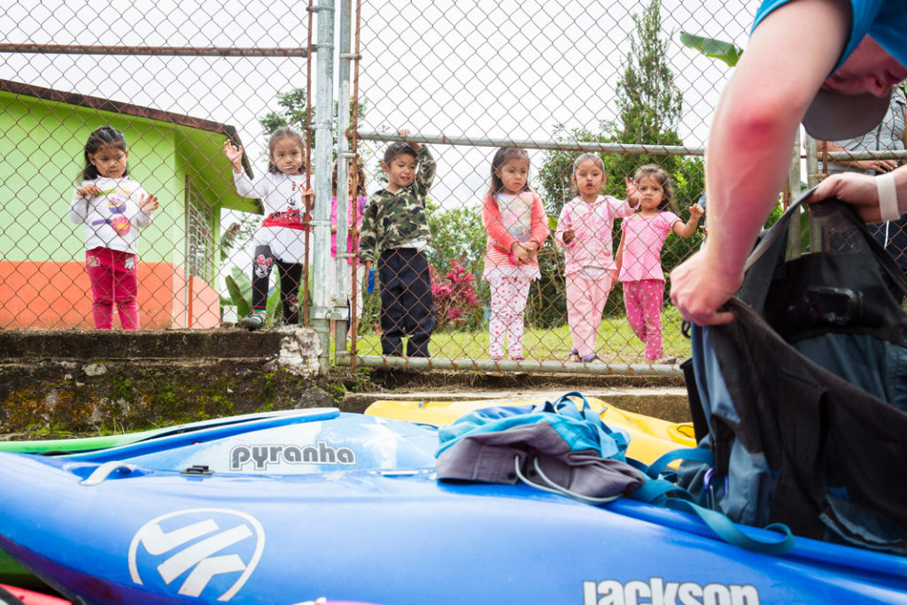 children looking at a man with his kayak
