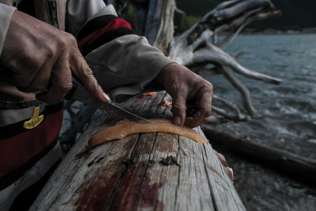 man cutting salmon on a log