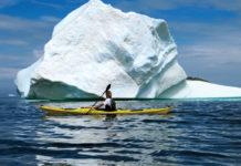 woman sea kayaking beside an iceberg
