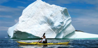 woman sea kayaking beside an iceberg