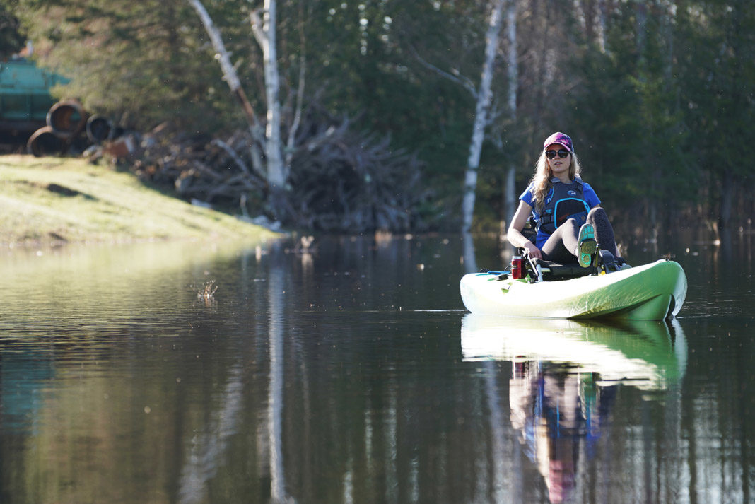 woman paddling a green ocean kayak
