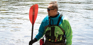 man holding a kayak paddle and wearing paddling gear