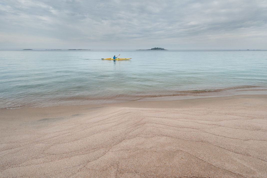 man paddling in the distance from a beach