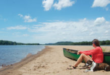 woman sitting with her dog on a beach beside a canoe