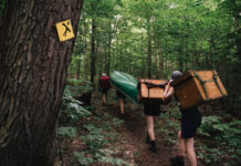 paddlers carrying gear on a portage trail