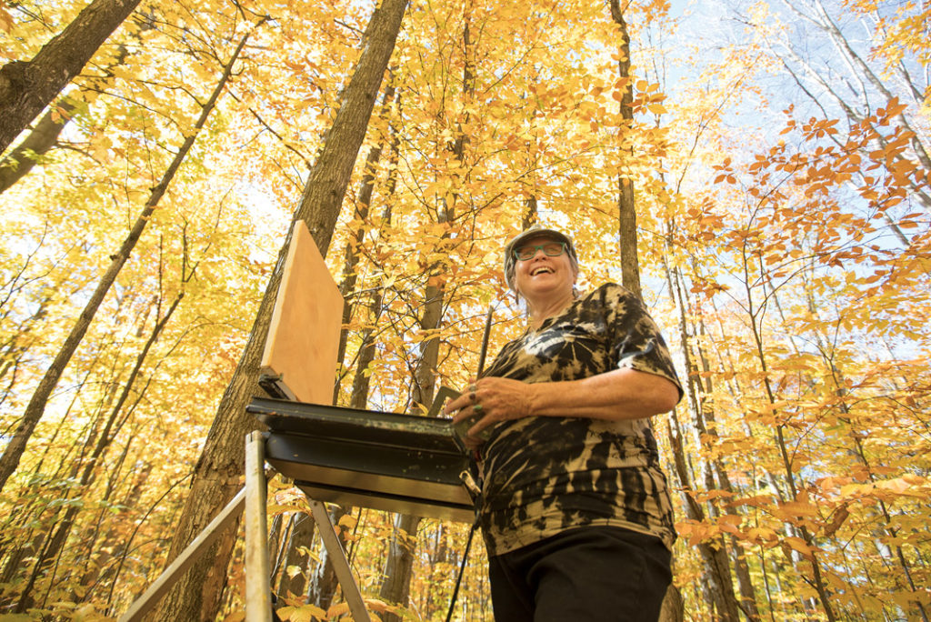 Sorensen painting surrounded by trees with yellow leaves